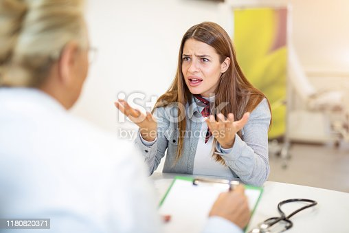 Frustrated young woman talking with her doctor.