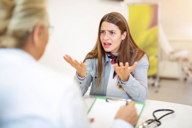 Frustrated young woman talking with her doctor. Frustrated young woman talking with her doctor. displeased stock pictures, royalty-free photos & images