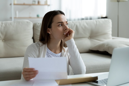 Thoughtful unhappy frustrated young woman holding paper letter with banking termination notification or eviction notice, thinking of financial problems bankruptcy or unexpected bad news alone at home.