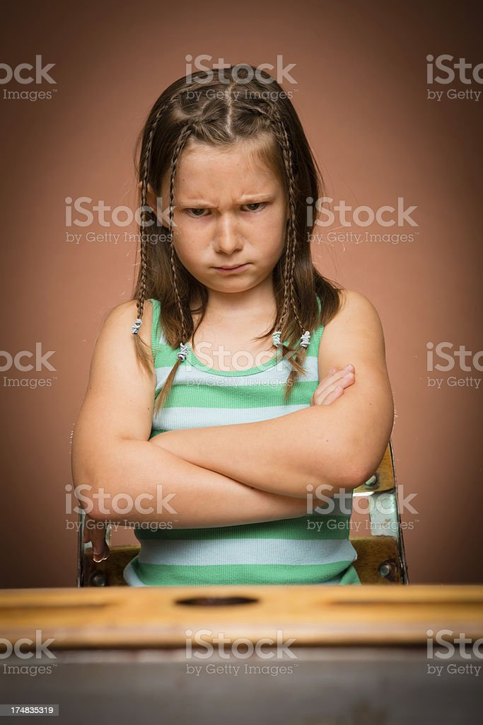 Frustrated/Angry Young Girl Student Sitting at School Desk royalty-free stock photo