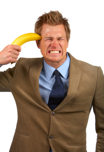 Frustration Businessman Trying To Attempt Suicide With Banana Gun Stock Photo - Download Image Now