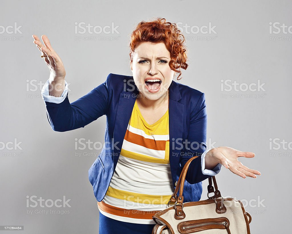 Frustration Portrait of irritated young woman screaming at the camera. Studio shot, grey background. 25-29 Years Stock Photo