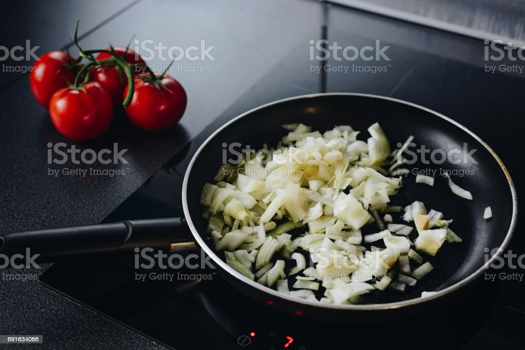 Frying chopped onion on olive oil stock photo