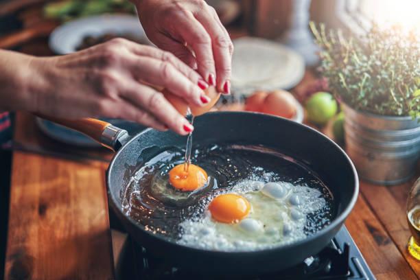 freír el huevo en una cacerola cocinar en cocina doméstica - desayuno fotografías e imágenes de stock