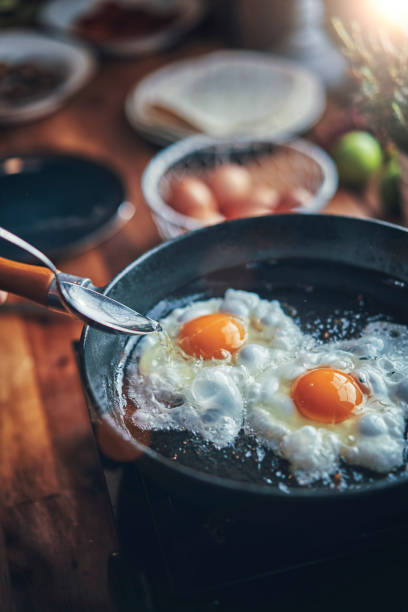 Frying Egg in a Cooking Pan in Domestic Kitchen stock photo