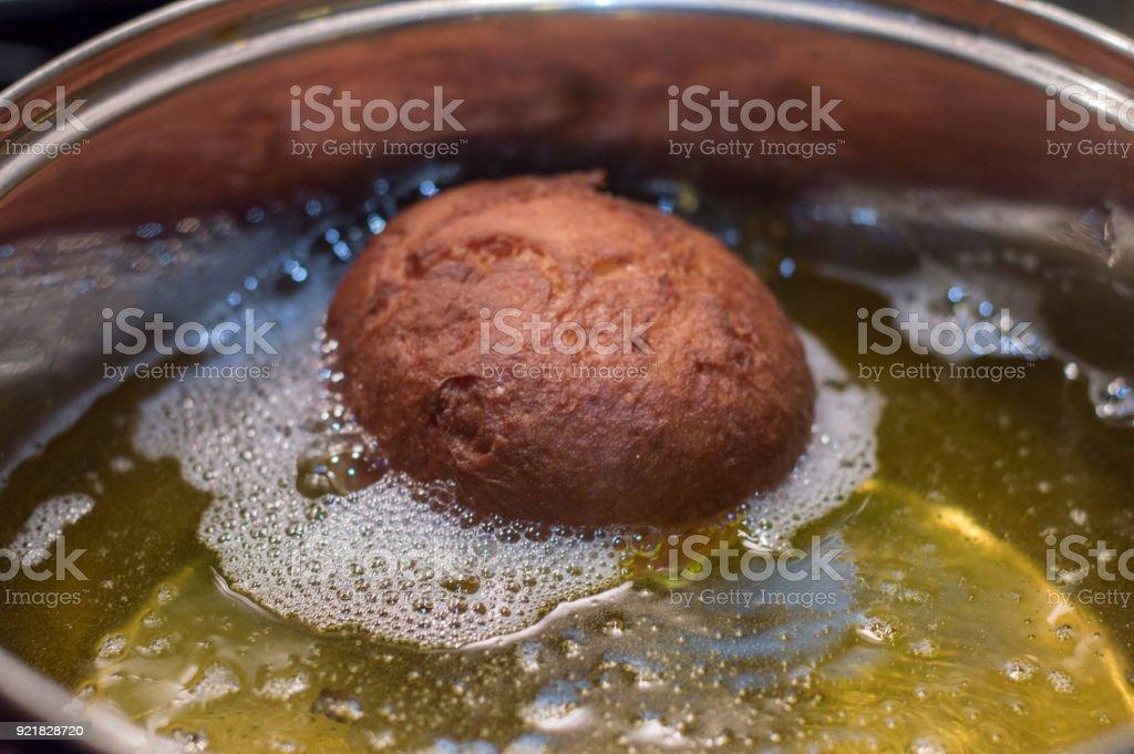 Frying paczek in metal pot. Paczki is Polish donuts.