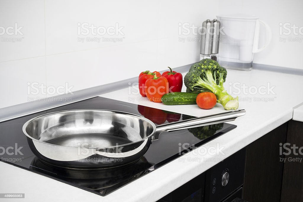 Frying pan and vegetables in modern with induction stove stock photo