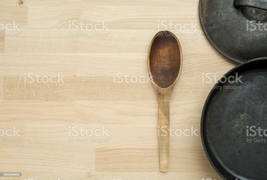 Frying pan and wooden spoon on kitchen table ロイヤリティフリーストックフォト