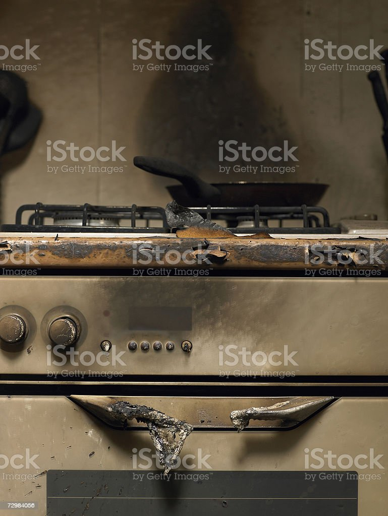 Frying pan on smoke stained cooker in kitchen after fire stock photo