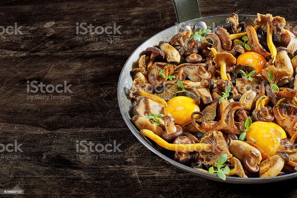 Frying pan steel with mushrooms and soft egg yolks. stock photo