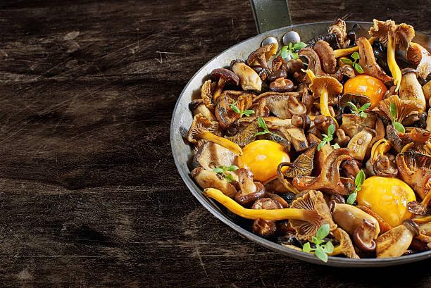 frying pan steel with mushrooms and soft egg yolks. - pilzpfanne stock-fotos und bilder