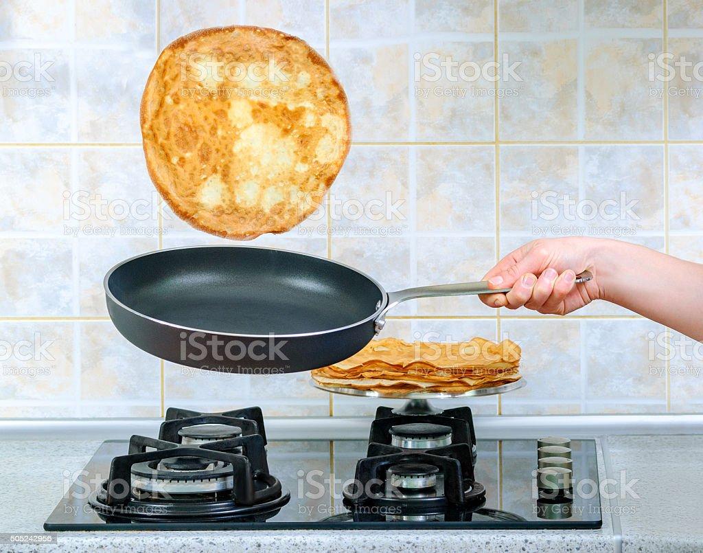 Frying pan with flying pancake stock photo