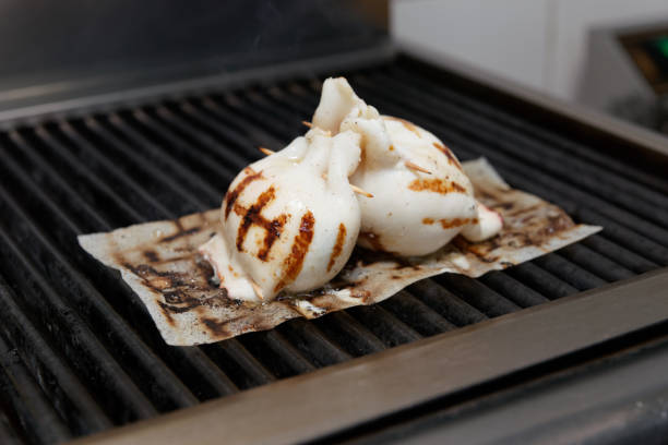 Frying stuffed squids on grill stock photo