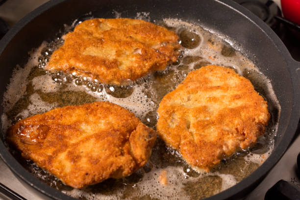 Frying wiener schnitzel in a hot pan stock photo
