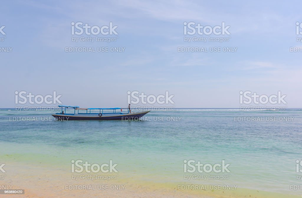 Fshermen driving a long-tail boat in the turkouise ocean - Royalty-free Asia Stock Photo