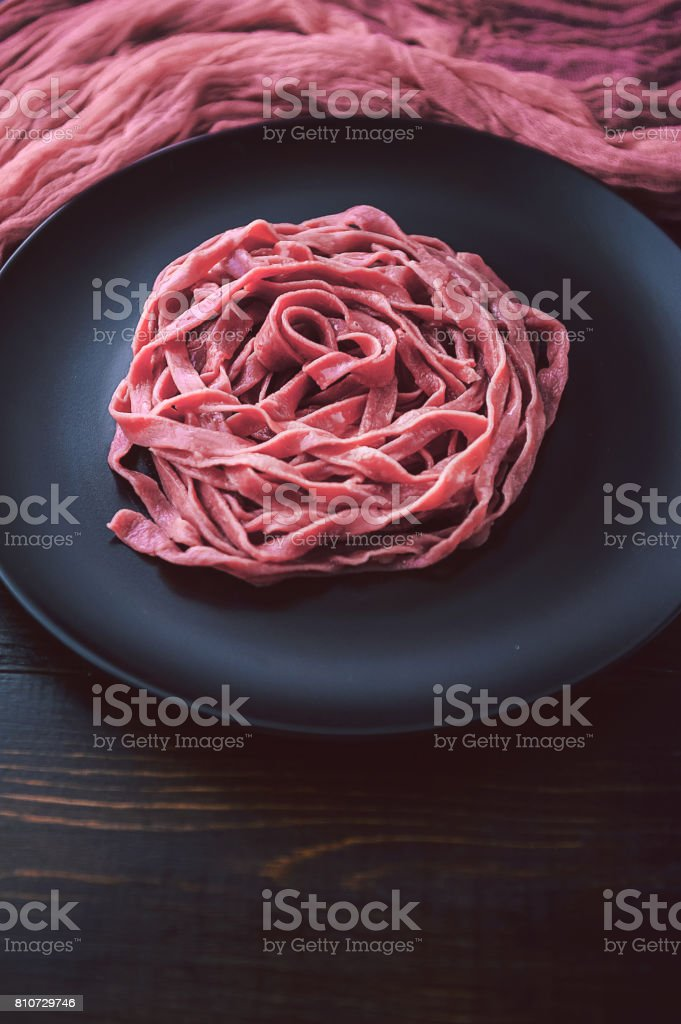 Fuchs delicacy pasta with home-made beet juice, cranberries, essences of French wine with feta cheese and flax seed stock photo