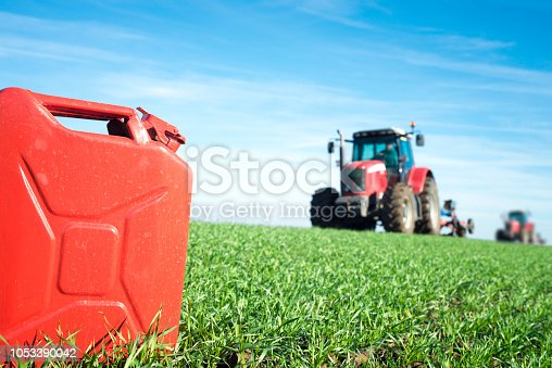 Gas can and tractor working in the field. Biodiesel and petrol production.