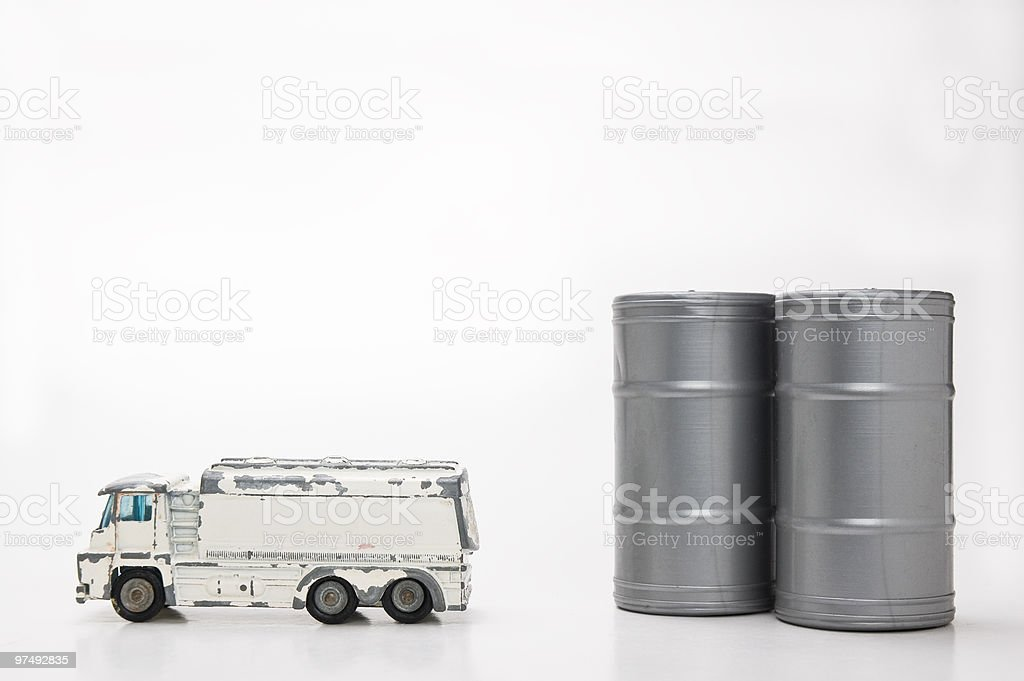 Fuel economy concept: minature tanker truck next to oil drums. royalty-free stock photo