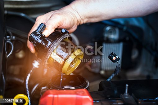 Car mechanic check the fuel filter at diesel engine. service or Preventive maintenance.