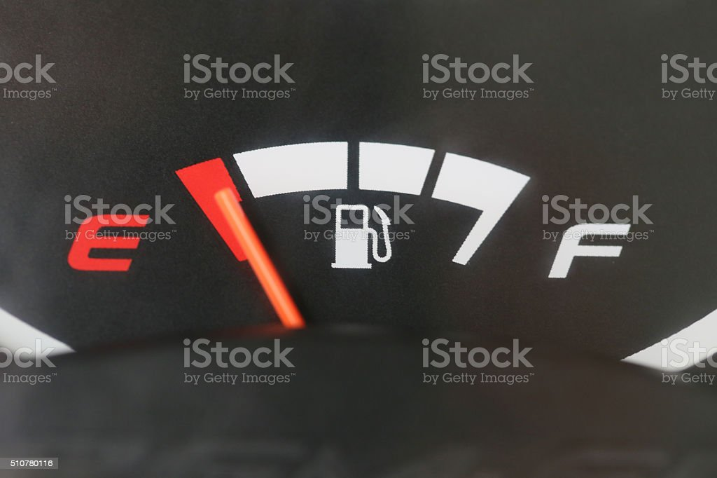 Fuel gauge with warning indicating low fuel tank. stock photo