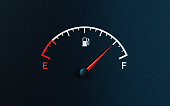 istock Fuel Gauge's Red Needle Indicating Full Gas Tank on Black Background 1262374947