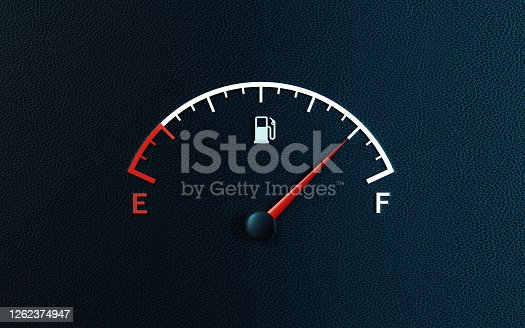 Fuel gauge's red needle indicating full gas tank on black background. Horizontal composition with copy space.