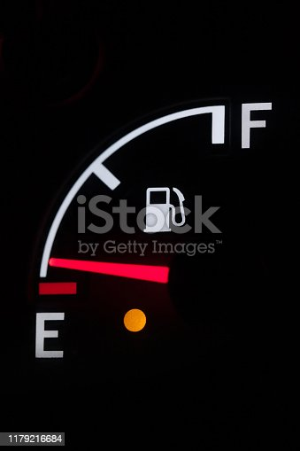 istock fuel indicator arrow shows empty tank, red arrow on a black background, close up 1179216684