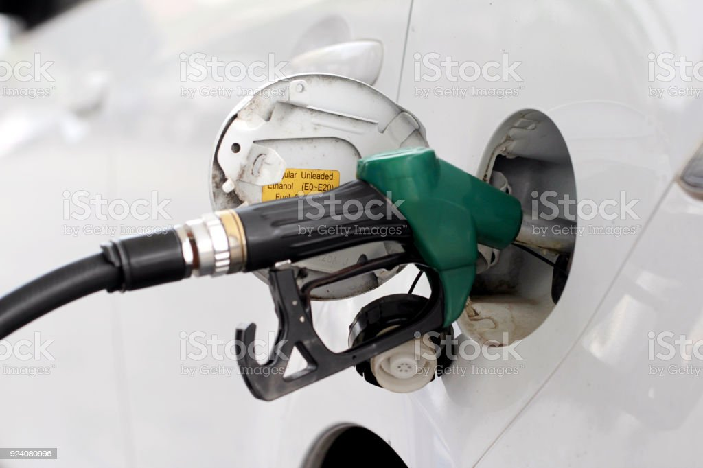fuel nozzle is filling oil to car stock photo
