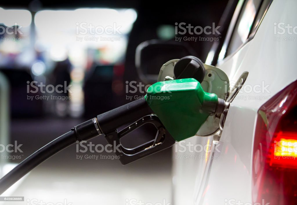 Fuel nozzles adding gasoline fuel in car at a pump gas station stock photo