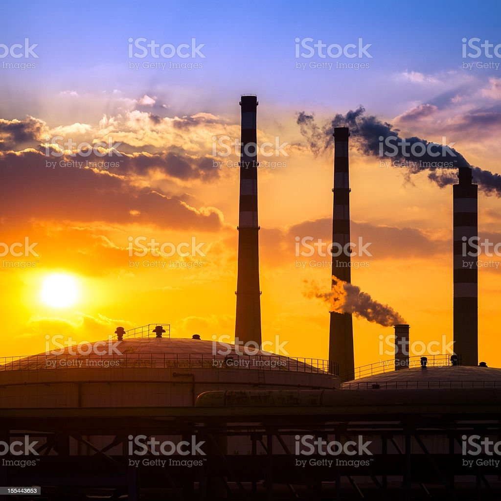 Fuel storage area and power plant at sunset stock photo