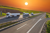 Three white gasoline tanker trucks in line driving towards the sun. Fast delivery on the freeway at beautiful sunset. Freight scene on the motorway near Belgrade, Serbia.