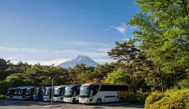 グリーン シーズンのフォア グラウンドを駐車場バスで早朝の富士 - バス ストックフォトと画像