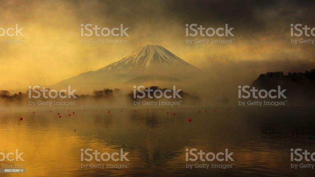 Fujisan oder Mount Fuji bei Sonnenaufgang mit dunklen Wolken und Nebel vom See Shoji – Foto
