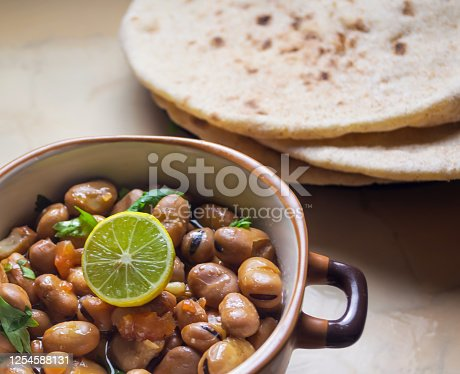 1215965415 istock photo Ful Medames - Dish of Egyptian fava beans with lemon ,cumin ,vegetable 1254588131