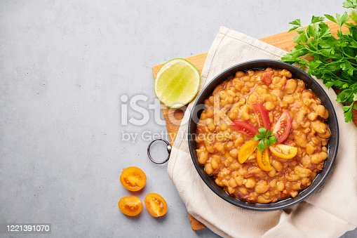 1215965415 istock photo Ful Medames or Fava Beans in black bowl at grey backdrop. Foul Mudammas is a Egyptian, Lebanese, Syrian, Eritrean, Israeli cuisines breakfast dish of cooked beans with cumin, tomatoes, parsley 1221391070