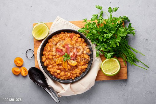 1215965415 istock photo Ful Medames or Fava Beans in black bowl at grey backdrop. Foul Mudammas is a Egyptian, Lebanese, Syrian, Eritrean, Israeli cuisines breakfast dish of cooked beans with cumin, tomatoes, parsley 1221391076