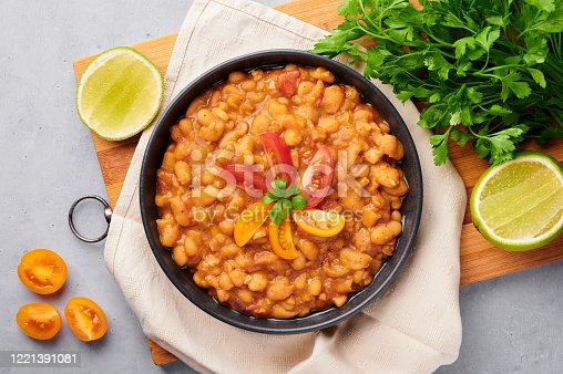 1215965415 istock photo Ful Medames or Fava Beans in black bowl at grey backdrop. Foul Mudammas is a Egyptian, Lebanese, Syrian, Eritrean, Israeli cuisines breakfast dish of cooked beans with cumin, tomatoes, parsley 1221391081