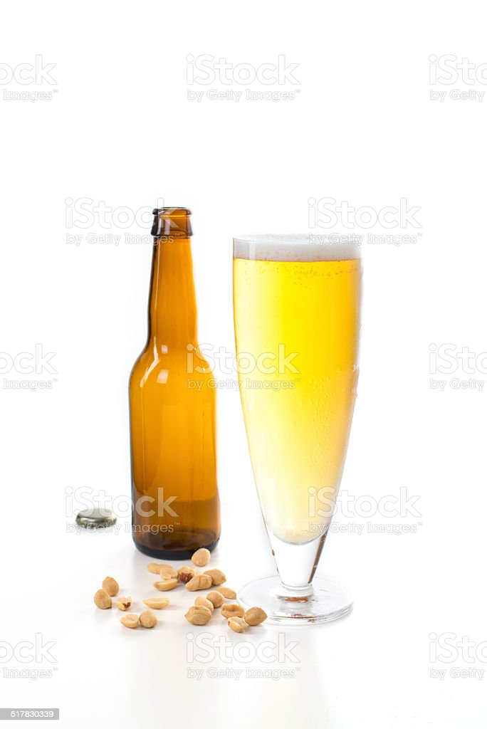 Full beer glass with nuts on the table stock photo