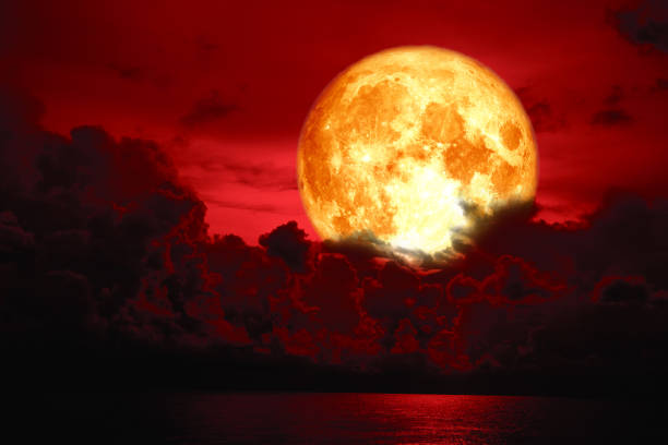 full blood moon over silhouette heap cloud on the sea stock photo