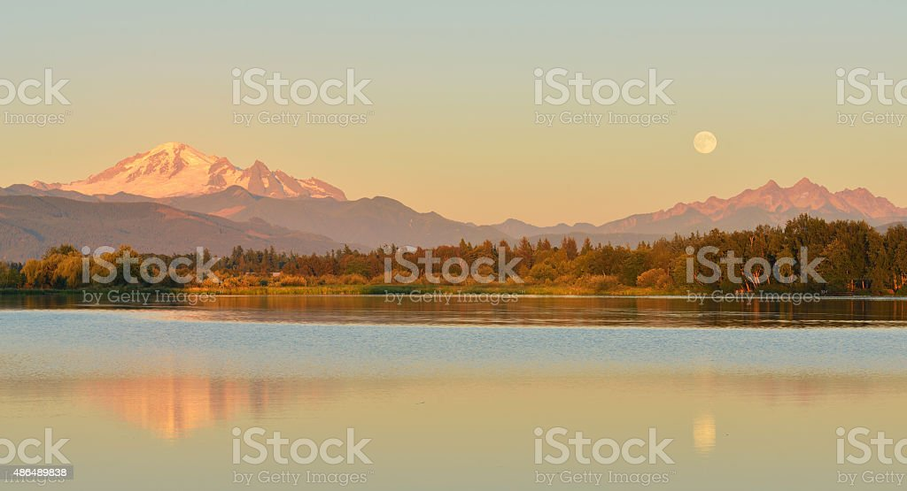 Full Blue Moon over Mt. Baker and Three Sisters Mountain stock photo