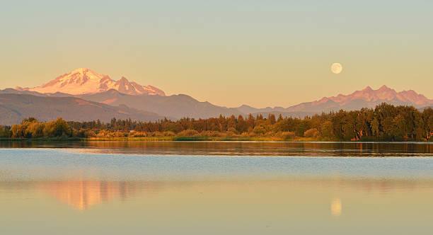 pleine lune bleue au-dessus de le mont baker et les montagnes three sisters - mont baker photos et images de collection