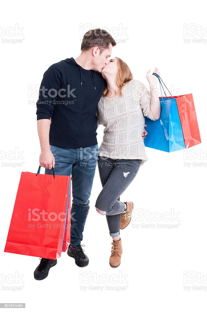 Full body couple holding shopping bags and kissing photo libre de droits