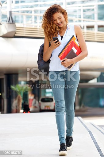 Full body portrait of happy female student walking outside with cellphone