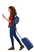 istock Full body happy travel woman walking with cellphone and luggage against isolated white background 1035689406