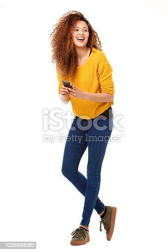 Full body portrait of happy woman with cellphone laughing against isolated white background