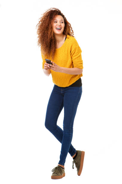 Full body happy woman with cellphone laughing against isolated white background - foto stock