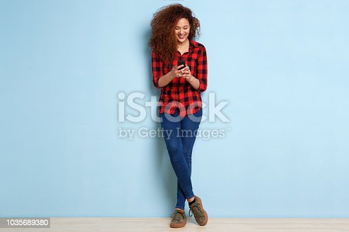 istock Full body happy young woman looking at mobile phone 1035689380