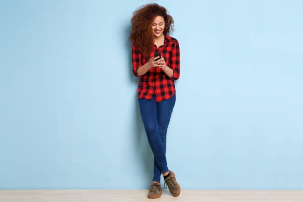 corpo inteiro feliz jovem olhando para o telefone móvel - lifestyle color background - fotografias e filmes do acervo