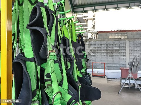 istock full body harness hanging on the rack,personal protective equipment for  height work 1142438461