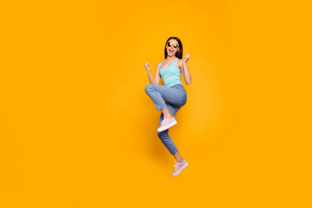 full body length size studio photo portrait of glad positive bright vivid shine with open mouth optimistic lovely she her lady jumping up raising fists isolated vibrant background - smile woman open mouth foto e immagini stock